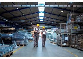 工厂工人走过大的生产大厅交谈着_11034311