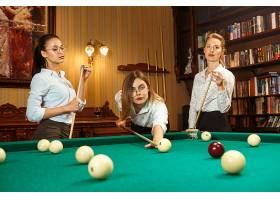 年轻微笑的女人下班后在办公室或家里打台球_11314331