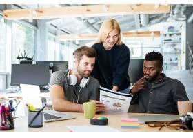 年輕快樂的同事們坐在辦公室一起工作_8078293