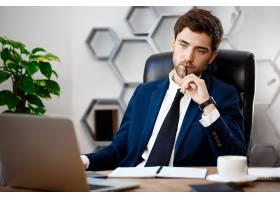 年轻成功的商人坐在工作场所有办公室背景_7857709