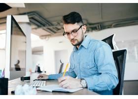 年轻漂亮的黑发男子戴着眼镜在办公室里用_9960970