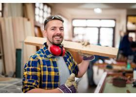 开心的木匠微笑着在他的木工车间里拿着木料_11135353