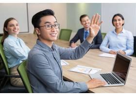 微笑的商人在会议上举手_1022722