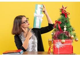 微笑的女商人戴着眼镜指着她的礼物坐_13408093