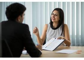 微笑的年轻女商人向合伙人展示合同_3801756