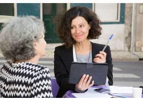 微笑的年轻顾问向年长的客户提供钢笔_4332902