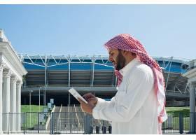 微笑的阿拉伯富人在城市里买房地产_9263971