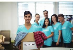 志愿者在捐赠箱里拿着衣服_1005891