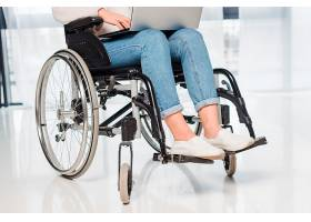 使用数字平板电脑的坐在轮椅上的残疾妇女的_4399985