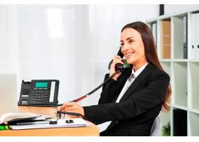 办公室里年轻的女商人边讲电话边微笑_3930709