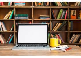 图书馆木桌上放着文具的咖啡杯和笔记本电脑_3553759