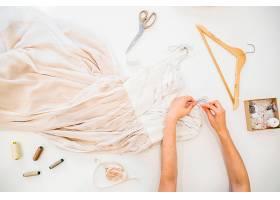 一位时装设计师在白色背景下用手处理衣服的_2766468