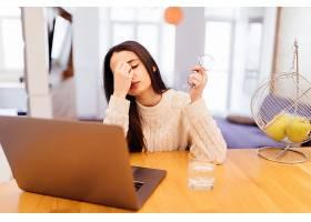 一位疲惫的妇女坐在家里的木桌旁在笔记本_9186323
