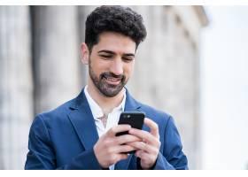 一位商人站在户外街道上使用手机的肖像商_13001869