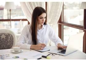 一位年轻的黑发女商人的前视图她正在笔记_6449750