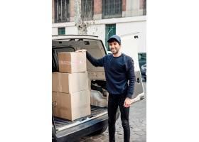 一位快乐的送货员站在拿着纸箱的车辆附近的_2675638