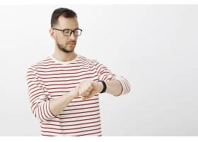 一位戴着眼镜的忙碌专注的商人看着数字手_10176100