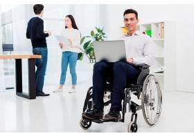 一位面带微笑的残疾年轻商人坐在轮椅上手_4400036