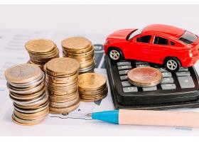 一叠硬币计算器模板上的玩具车和钢笔_3090794