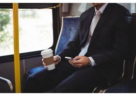 一名商人手持一次性咖啡杯使用手机_8402321