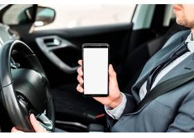 一名商人驾驶汽车展示白色显示屏手机的特写_3735217