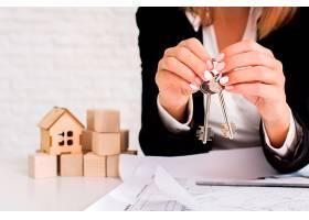 一名妇女手持一套带有木制立方体的钥匙_5240899