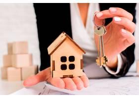 一名妇女手持一套钥匙和木屋_5240901