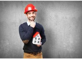 一名戴着红色头盔手里拿着一座小房子的男_990771