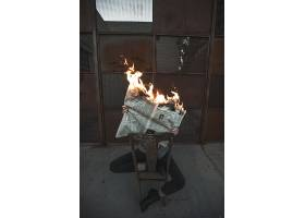 一名男性坐在椅子上阅读燃烧的报纸概念的垂_8070406