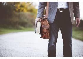 一名男性身着西装手持圣经站着的特写镜头_13005953