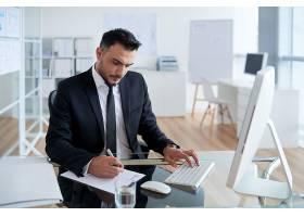 一名穿着西装的高加索男子坐在办公室里在_5839579