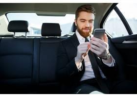 一名西装革履的男子看着手中的手机_7859655