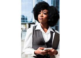 一幅非洲年轻女商人的肖像她手里拿着手机_4767853