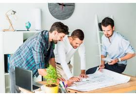 一群男性建筑师在办公室准备蓝图_2509477