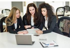 三个在现代办公室里一起工作的女商人_1174194