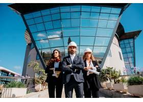 三位建筑师站在大楼前面窗户很大_1358382