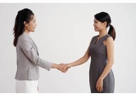 两名亚洲女商人站在室内微笑着握手_5576929
