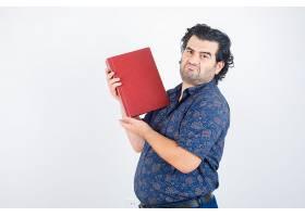 中年男子把书放在胸前穿着衬衫看起来犹豫_13464087