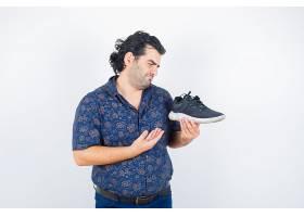 中年男子穿着衬衫拿着鞋子看起来很严肃_13464133