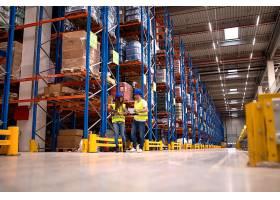 仓库工作人员讨论物流和面向市场的配送包裹_11451327