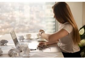 超负荷工作的女商人看着手表检查时间以赶_3938715