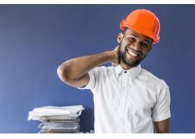 非裔美国男性建筑师站在工作场所的蓝色墙上_2601889