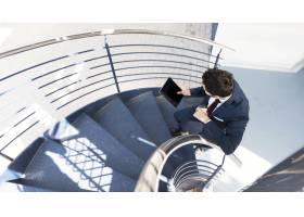 顶视人手持平板电脑站在楼梯上_5236716
