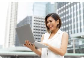 穿着商务女装的漂亮可爱女孩用笔记本电脑微_5392798