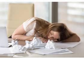 精疲力竭的妇女在办公室过度工作后睡在办公_3938721