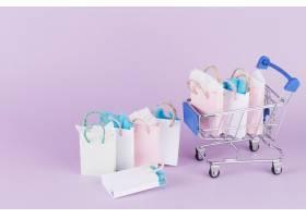 粉色背景的购物车里有许多五颜六色的纸质购_2934688