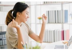 美丽微笑的亚洲年轻女子在家中客厅的办公桌_3441247