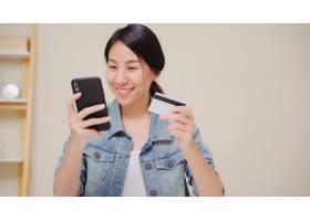 美丽的亚洲女人用智能手机刷卡网购穿着休_4396320