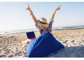 美丽的年轻女子在热带海滩上用笔记本电脑工_9686730