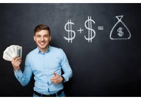 英俊的男子站在黑板上拿着抽出的美元概念_7678764